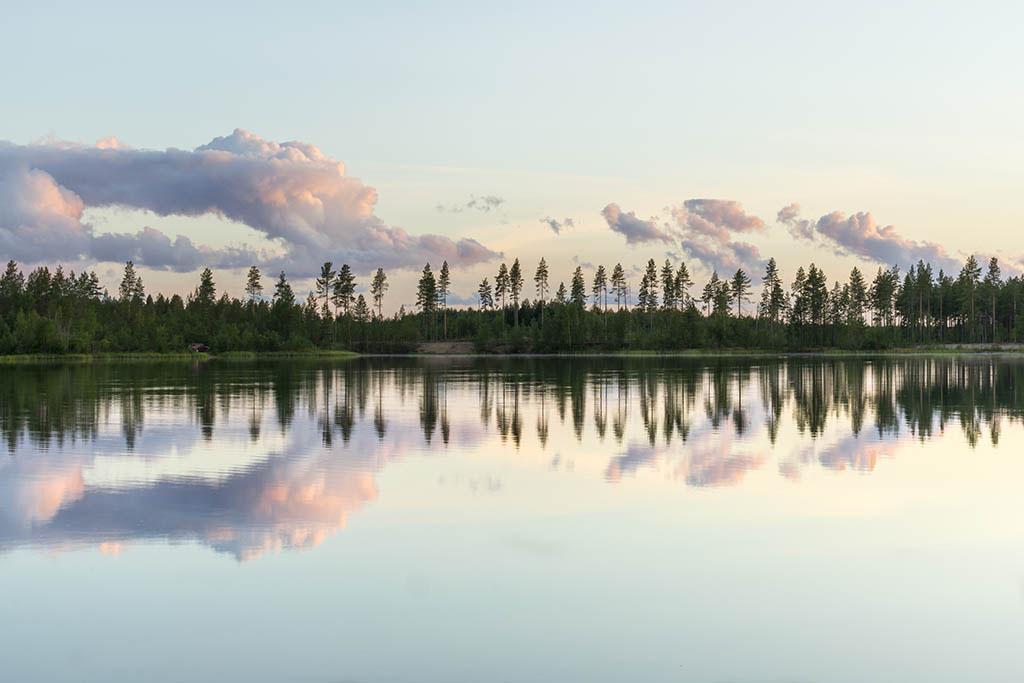 Alberi e nuvole riflesse su un lago in Finlandia