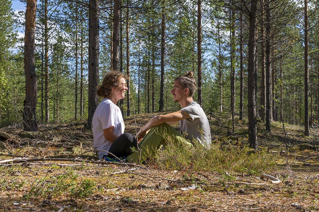 Marco e Chiara seduti di fronte nel bosco