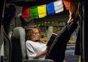 Chiara legge un libro in van con le bandiere tibetane